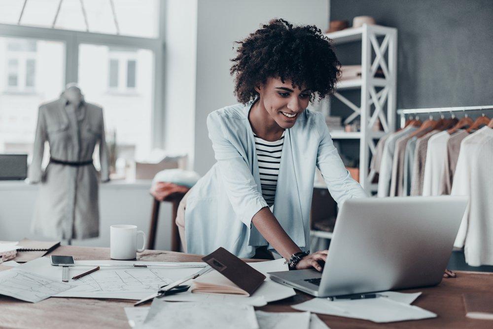 Respondendo por e-mail comercial. Jovem mulher africana trabalhando usando computador e sorrindo enquanto está em oficina